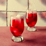 Cold cherry drink with ice cubes in glasses, on pink background Royalty Free Stock Images
