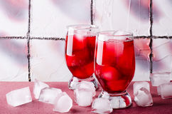 Cold cherry drink with ice cubes in glasses, on pink background Royalty Free Stock Photos