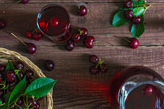Cold cherry juice in a glass and pitcher with cherries inside on wooden table. top view. Cold cherry juice in a glass and pitcher with cherries inside on wooden Stock Image