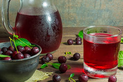 Cold cherry juice in a glass and pitcher on wooden table. With ripe berries in pottery bowl Royalty Free Stock Photo