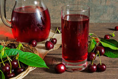 Cold cherry juice in a glass and pitcher on wooden table Stock Images