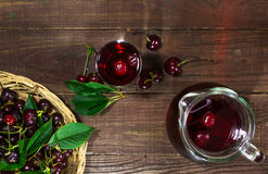 Cold cherry juice in a glass and pitcher on wooden table with ripe berries in wicker basket. top view Stock Images