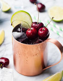 Cold cherry Moscow Mules cocktail with ginger beer, vodka, lime Marble background Copy space. Stock Photo