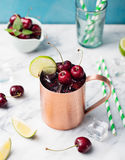 Cold cherry Moscow Mules cocktail with ginger beer, vodka, lime Marble background Copy space Stock Photos