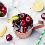 Cold cherry Moscow Mules cocktail with ginger beer, vodka, lime Marble background Top view Stock Photography
