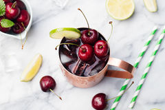 Cold cherry Moscow Mules cocktail with ginger beer, vodka, lime Marble background Top view Royalty Free Stock Photography