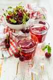 Cold cherry summer drink in glasses. White wood background Royalty Free Stock Photo