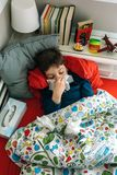 Cold child lying on the bed Royalty Free Stock Image