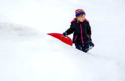 Cold child walking in the snow with sled Stock Photo