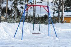 Cold, without children cold Playground with lonely standing swings on a chain. the snow and emptiness. Winter, cold, without children cold Playground with lonely stock photo