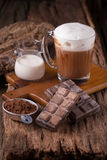 Cold Chocolate Milk drink and chocolate bar on wooden background Royalty Free Stock Image