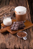Cold Chocolate Milk drink and chocolate bar on wooden background Royalty Free Stock Images