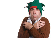 Cold Christmas. A man is cold and wearing only a sweater, an elf hat and a white scarf, all of which don't match, isolated against a white background Royalty Free Stock Photography