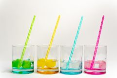 Cold, clean water in rainbow colored glasses. Colored glasses in a row with colored ice and drinking straws filled with cold, fresh water stock image