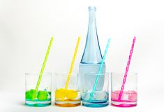 Cold, clean water in rainbow colored glasses. Colored glasses in a row with colored ice and drinking straws filled with cold, fresh water stock photo