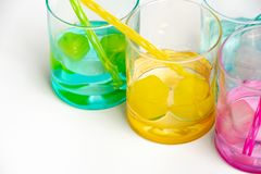 Cold, clean water in rainbow colored glasses. Colored glasses in a row with colored ice and drinking straws filled with cold, fresh water stock photos