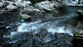 Cold clear water of mountain river in winter time, icicles on boulder stock video