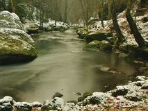 Cold Clear Water Of Mountain River In Winter Time, Icicles On Boulder Royalty Free Stock Image