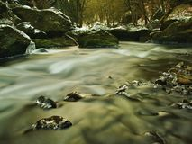 Cold Clear Water Of Mountain River In Winter Time, Icicles On Boulder Stock Photo