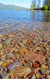 Cold, clear water shows rocks lying around the bottom of the lake. Royalty Free Stock Photo