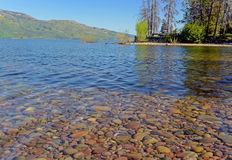 Cold, clear water shows rocks lying around the bottom of the lake. Stock Images