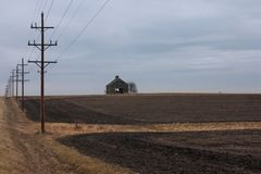 End of the Autumn Harvest. On a cold cloudy day in autumn, telephone poles lead the way to a withered barn. Th barn which stands in recently plowed farm fields stock images