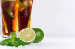 Cold cocktail cuba libre in two long glasses with straw, pieces lime on soft modern white background, closeup, texture. Cold cocktail cuba libre in two long Stock Photography