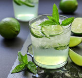 Cold cocktail with lemon liqueur, lime, tonic, ice on dark background. royalty free stock image