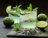 Cold cocktail with lemon liqueur, lime, tonic, ice on dark background. royalty free stock photography