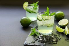 Cold cocktail with lemon liqueur, lime, tonic, ice on dark background. royalty free stock photos