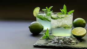 Cold cocktail with lemon liqueur, lime, tonic, ice on dark background. Stock Images
