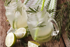 Cold cocktail with lime, ice and rosemary close up in a jar. Hor Stock Images