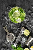 Cold cocktail with lime, mint, ice. Drink making tools Royalty Free Stock Photo