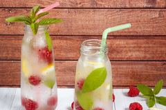 Cold cocktail with raspberries, lemon and mint. Wooden background Stock Image