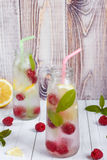 Cold cocktail with raspberries, lemon and mint. Wooden background Stock Photography