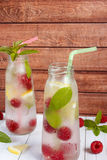 Cold cocktail with raspberries, lemon and mint. Wooden background Stock Photos