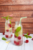 Cold cocktail with raspberries, lemon and mint. Wooden background Royalty Free Stock Photos