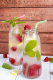 Cold cocktail with raspberries, lemon and mint. Wooden background Royalty Free Stock Image