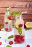 Cold cocktail with raspberries, lemon and mint. Wooden background Royalty Free Stock Photography