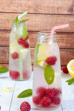 Cold cocktail with raspberries, lemon and mint. Wooden background Stock Images