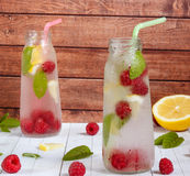 Cold cocktail with raspberries, lemon and mint. Wooden background Royalty Free Stock Images