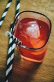 Cold cocktail red-coloured with ice cubes and drinking straws Royalty Free Stock Photos