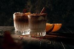 Cold cocktail sprinkled with cinnamon on a dark background. Low key photography. royalty free stock images