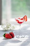 Cold cocktail with vodka, strawberry syrup, fresh strawberries and crushed ice in glasses on a light background Stock Photos