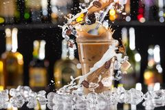 Cold coffee drink with ice, beans and splash. stock image