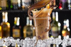 Cold coffee drink with ice, beans and splash. royalty free stock image