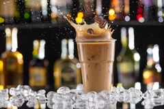 Cold coffee drink with ice, beans and splash Royalty Free Stock Photos