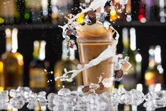 Cold coffee drink with ice, beans and splash Stock Photos
