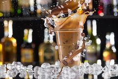 Cold coffee drink with ice, beans and splash. stock photos