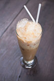 Cold coffee drink with ice on wood Stock Photography